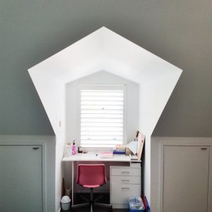 Desk positioned in niche at dormer window