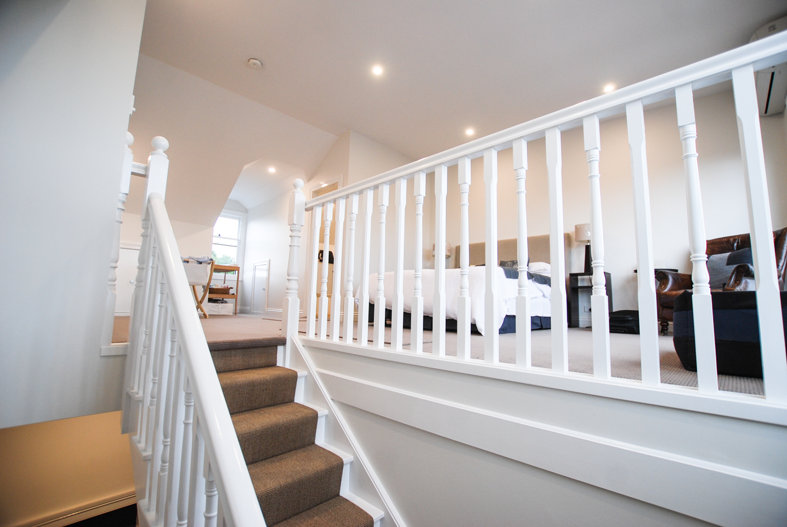 Attic staircase with white banister and railing - view up to habitable attic room