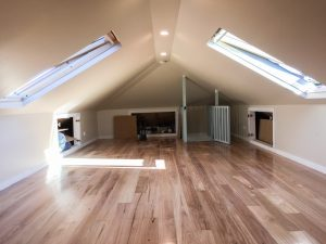 Large habitable attic with two skylights and inbuilt storage cupboards in eaves